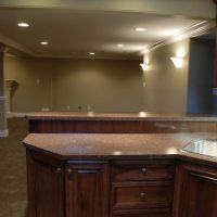 cabinetry with elevated bar in basement